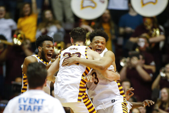 Winthrop guard Micheal Anumba, right, hugs guard Kyle Zunic as they celebrate after winning the Big South tournament championship over Hampton in an NCAA college basketball game in Rock Hill, S.C., Sunday, March 8, 2020. (AP Photo/Nell Redmond)