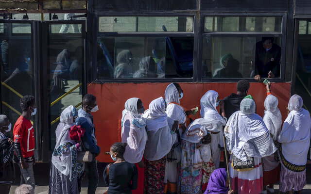 Passengers queue to get on a bus in the capital Addis Ababa, Ethiopia Friday, Nov. 6, 2020. Ethiopia's prime minister says airstrikes have been carried out against the forces of the country's Tigray region, asserting that the strikes in multiple locations