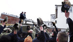 Sailors stationed with the historic frigate U.S.S. Constitution doff their caps as World War II tank gunner Clarence Smoyer enters the Charlestown Naval Shipyard in Boston, Wednesday, Feb. 20, 2019. The 95-year-old veteran was surprised with a ride through the streets of Boston in a Sherman tank, one of the tanks most widely used by the U.S. during the war. (AP Photo/Charles Krupa)
