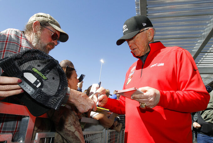 Race team owner Joe Gibbs, right, signs autographs for fans prior to the start of the NASCAR Cup Series auto race at ISM Raceway, Sunday, March 10, 2019, in Avondale, Ariz. (AP Photo/Ralph Freso)