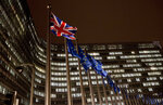 A Union flag, left, flaps in the wind alongside EU flags in front of European Commission headquarters in Brussels, Wednesday, Nov. 21, 2018. British Prime Minister Theresa May meets with European Commission President Jean-Claude Juncker on Wednesday evening in a bid to finalize a Brexit agreement as she continues to battle domestic critics of the draft deal. (AP Photo/Virginia Mayo)
