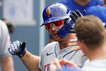 New York Mets' Pete Alonso is congratulated by teammates after hitting a two-run home run against the Los Angeles Dodgers during the seventh inning of a baseball game in Los Angeles, Saturday, Aug. 21, 2021. (AP Photo/Alex Gallardo)
