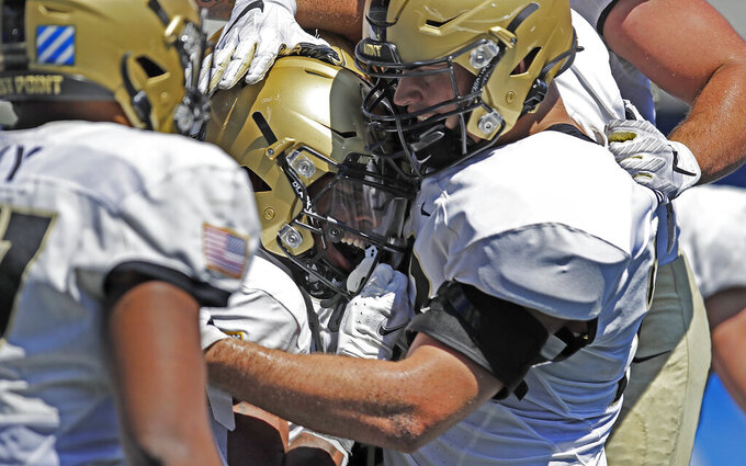 Army running back Braheam Murphy, center, celebrates with Zack Ward after scoring a touchdown against Georgia State during the second half of an NCAA football game Saturday, Sept. 4, 2021, in Atlanta. (AP Photo/Ben Margot)