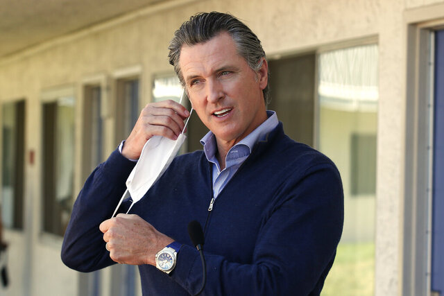 Gov. Gavin Newsom removes his face mask before giving an update on the state's initiative to provide housing for homeless Californians to help stem the coronavirus, during a visit to a Motel 6 participating in the program in Pittsburg, Calif., Tuesday, June 30, 2020. Newsom announced that more than 15,000 rooms have been acquired and more than 14,000 people have been given places to stay statewide under the Project Room key program started in April. The governor also said he plans to announce on Wednesday plans to