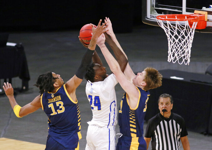 UC Santa Barbara's Robinson Idehen (24) is fouled as UC Irvine's Dean Keeler (31) and Austin Johnson defend during the first half of an NCAA college basketball game for the championship of the Big West Conference men's tournament Saturday, March 13, 2021, in Las Vegas. (AP Photo/Ronda Churchill)