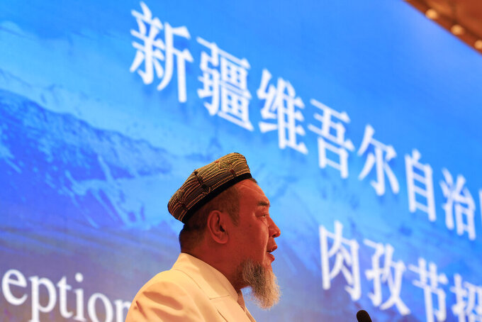 Abdureqip Tomurniyaz, who heads the association and the school for Islamic studies in Xinjiang, speaks during a government reception held for the Eid al-Fitr festival in Beijing on Thursday, May 13, 2021. Muslim leaders from the Xinjiang region rejected Western allegations that China is suppressing religious freedom, speaking at a reception Thursday for foreign diplomats and media at the end of the holy month of Ramadan. Chinese characters at top reads Xinjiang Uyghur Autonomous Region. (AP Photo/Ng Han Guan)