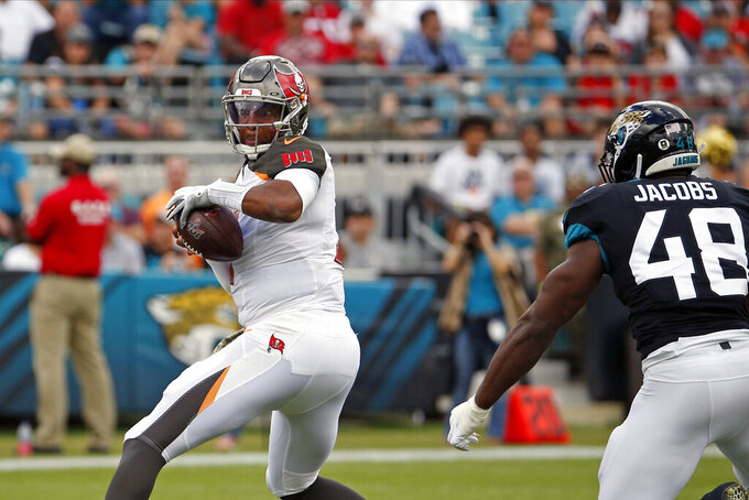 Tampa Bay Buccaneers quarterback Jameis Winston, left, looks for a receiver as he is pressured by Jacksonville Jaguars outside linebacker Leon Jacobs (48) during the first half of an NFL football game, Sunday, Dec. 1, 2019, in Jacksonville, Fla. (AP Photo/Stephen B. Morton)