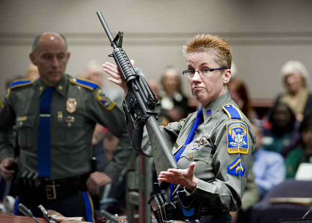 FILE - In this Jan. 28, 2013, file photo, firearms training unit Detective Barbara J. Mattson, of the Connecticut State Police, holds up a Bushmaster AR-15 rifle, produced by Remington Arms  and the same make and model of gun used by Adam Lanza in the Sandy Hook School shooting, for a demonstration during a hearing of a legislative subcommittee reviewing gun laws, at the Legislative Office Building in Hartford, Conn. Remington Arms has filed for Chapter 11 bankruptcy protection, Tuesday, July 28, 2020,  for the second time in a little more than two years, despite a recent surge in gun demand. Remington is currently embroiled in a lawsuit involving the the 2012 Sandy Hook school shooting.  (AP Photo/Jessica Hill, File)