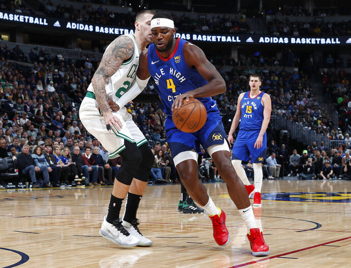 Denver Nuggets forward Paul Millsap drives against Boston Celtics forward Daniel Theis during the first half of an NBA basketball game Friday, Nov. 22, 2019, in Denver. (AP Photo/David Zalubowski)