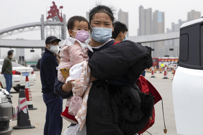 In this Thursday, April 2, 2020, photo, a woman holding a child walks away from the expressway gate at the border of Wuhan city in central China's Hubei province. Millions of Chinese workers are streaming back to factories, shops and offices but many still face anti-coronavirus controls that add to their financial losses and aggravation. In Wuhan police require a health check and documents from employers for returning workers. (AP Photo/Ng Han Guan)