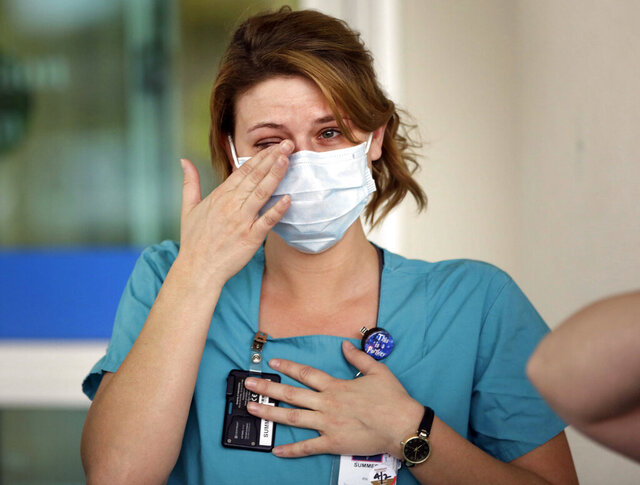 In this Thursday, April 2, 2020, photo, RN Summer Jones, wipes a tear away as she sees supporters cheer during an event called Headlights for Hope at Ascension St. John in Owasso, Okla. Cars crowded into the parking lot and turned headlights and hazards on, honked horns and cheered to thank medical personnel for their work in the COVID-19 outbreak. (Mike Simons/Tulsa World via AP)