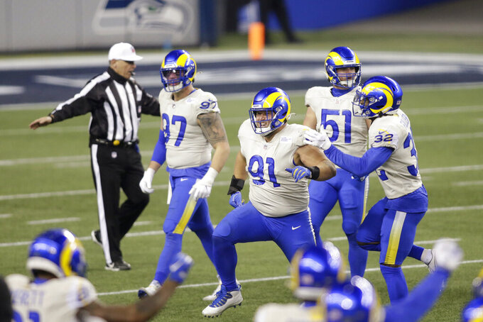 Los Angeles Rams' Greg Gaines (91) and teammates celebrate after defeating the Seattle Seahawks in an NFL wild-card playoff football game, Saturday, Jan. 9, 2021, in Seattle. (AP Photo/Scott Eklund)