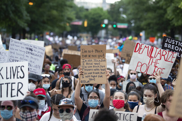 People carry signs as they march Monday, June 1, 2020, in Atlanta during a demonstration over the death of George Floyd who died after being restrained by Minneapolis police officers on May 25. (AP Photo/John Bazemore).