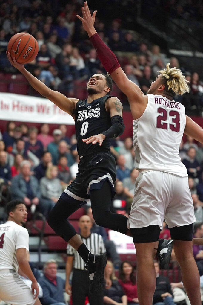 Gonzaga guard Geno Crandall (0) drives to the basket against Santa Clara center Ezekiel Richards (23) during the second half of an NCAA college basketball game Thursday, Jan. 24, 2019, in Santa Clara, Calif. Gonzaga won 98-39. (AP Photo/Tony Avelar)