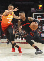 Portland Trail Blazers guard Damian Lillard, right, drives to the basket on Utah Jazz guard Dante Exum during the first half of an NBA basketball game in Portland, Ore., Wednesday, April 11, 2018. (AP Photo/Steve Dykes)