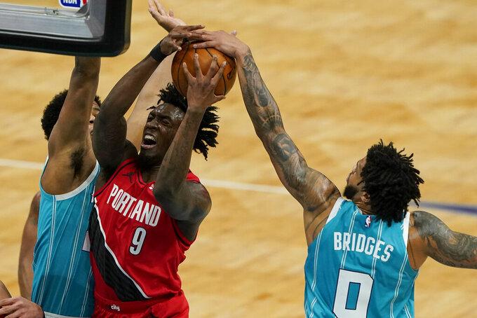 Charlotte Hornets forward Miles Bridges blocks a shot by Portland Trail Blazers forward Nassir Little (9) during the first half in an NBA basketball game on Sunday, April 18, 2021, in Charlotte, N.C. (AP Photo/Chris Carlson)