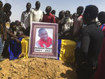 A family member, left, Mourn at the coffin of one of the victims who was killed this week at a protest during his funeral at a cemetery in N'Djamena, Chad, Saturday, May 1, 2021. Hundreds of chanting mourners carrying Chadian flags gathered Saturday to bury victims who were shot dead earlier this week amid demonstrations against the country's new military government .(AP Photo/Sunday Alamba)