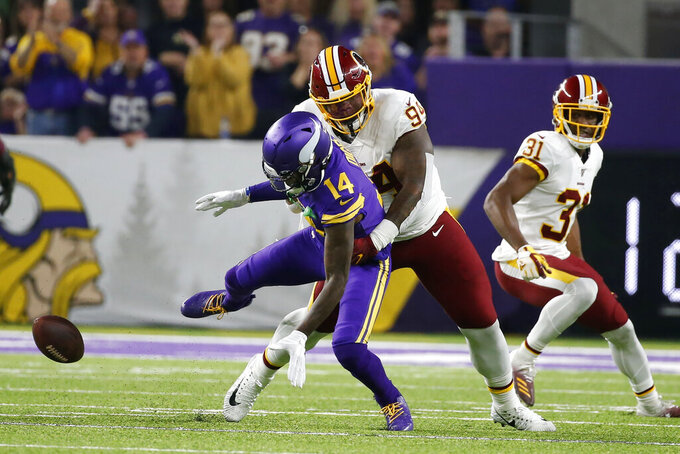 Minnesota Vikings wide receiver Stefon Diggs (14) fumbles the ball as he is tackled by Washington Redskins nose tackle Daron Payne (94) during the first half of an NFL football game, Thursday, Oct. 24, 2019, in Minneapolis. (AP Photo/Bruce Kluckhohn)