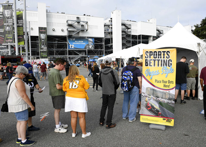 FILE - In this Oct. 7, 2018, file photo, fans line up next to a tent kiosk for legalized sports betting at the Dover International Speedway before the NASCAR Cup series auto race in Dover, Del. NASCAR is making its first big play in the world of expanded legal sports betting, hoping a sports data partnership will lead to gamblers being able to bet during races on much more than just who gets the checkered flag. Genius Sports has become the exclusive provider of NASCAR data to licensed sportsbooks, officials announced Friday, May 3, 2019. (AP Photo/Nick Wass, File)