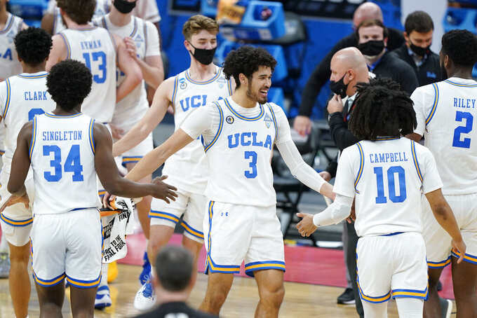 UCLA's Johnny Juzang (3) congratulates David Singleton (34) and Tyger Campbell (10) during a timeout in the first half of a college basketball game against Abilene Christian in the second round of the NCAA tournament at Bankers Life Fieldhouse in Indianapolis Monday, March 22, 2021. (AP Photo/Mark Humphrey)