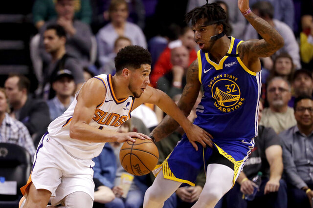 Phoenix Suns guard Devin Booker (1) drives around Golden State Warriors forward Marquese Chriss (32) during the first half of an NBA basketball game, Wednesday, Feb. 12, 2020, in Phoenix. (AP Photo/Matt York)