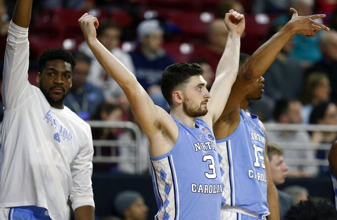 North Carolina's Andrew Platek (3) and Garrison Brooks (15) react on the bench during the first half of an NCAA college basketball game against Boston College in Boston, Tuesday, March 5, 2019. (AP Photo/Michael Dwyer)