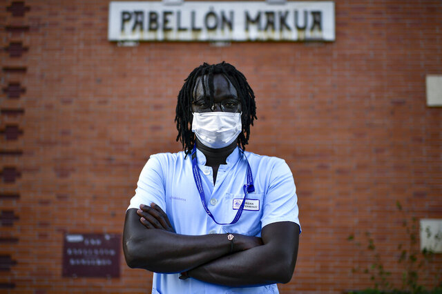Mbaye Babacar Diouf, poses for a photo wearing his nurse's uniform, at Basurto hospital, in Bilbao, northern Spain, Wednesday, Nov. 18, 2020. Mbaye Babacar Diouf's life as a migrant in Europe took a turn for the better when he was adopted in Spain at the age of 28. That enabled him to pay his debts to human traffickers, study nursing and find a job at a Spanish hospital. Now he's giving back to the community. In a Bilbao hospital he cares for COVID-19 patients. (AP Photo/Alvaro Barrientos)
