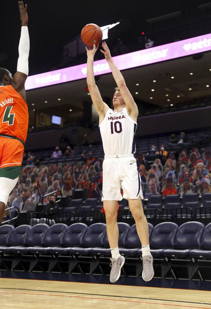 Virginia forward Sam Hauser (10) shoots over Miami guard Elijah Olaniyi (4) during an NCAA college basketball game Monday in Charlottesville, Va. (Andrew Shurtleff/The Daily Progress via AP, Pool)