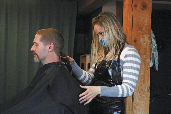 Ashley Story gives a haircut to client Michael Halstead on Friday, April 24, 2020, at her salon Short Cuts in Homer, Alaska. Story's is one of several Homer businesses to reopen their doors Friday according to relaxed state restrictions, while several others have opted to wait. (Megan Pacer/Homer News via AP)