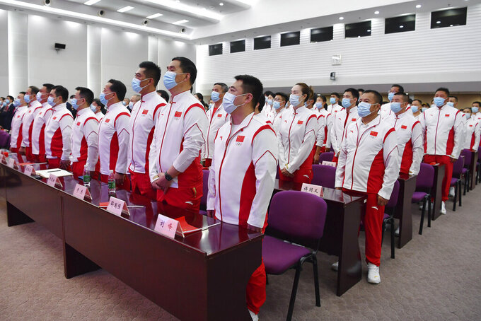 In this photo released by Xinhua News Agency, Members of the Chinese delegation for the upcoming Tokyo 2020 Olympic Games stand during the singing of the national anthem at a meeting in Beijing, China on Wednesday, July 14, 2021. China will send 431 athletes to the Tokyo Games as part of a 777-member delegation, its largest at an Olympics outside China, the official Xinhua News Agency said Wednesday. (Tao Xiyi/Xinhua via AP)