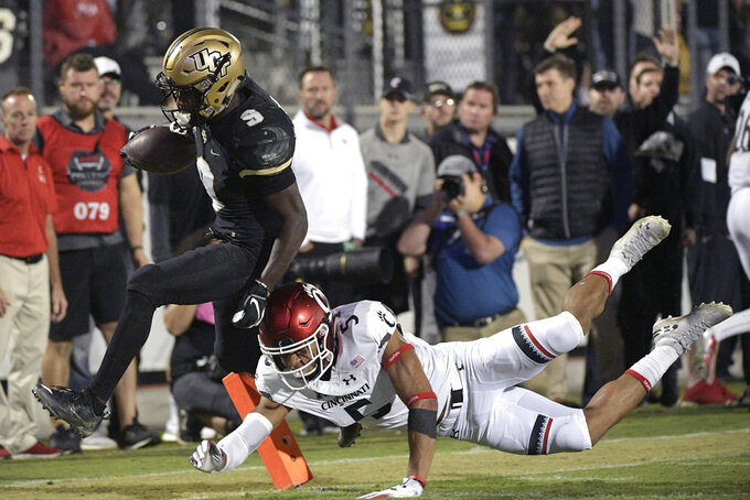 Central Florida running back Adrian Killins Jr. (9) scores a 42-yard touchdown in front of Cincinnati safety Darrick Forrest (5) after catching a pass during the second half of an NCAA college football game Saturday, Nov. 17, 2018, in Orlando, Fla. (AP Photo/Phelan M. Ebenhack)