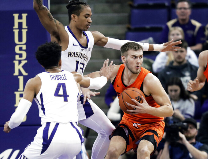 Oregon State forward Tres Tinkle, right, looks to pass around the defense of Washington guard Matisse Thybulle (4) and forward Hameir Wright (13) during the first half of an NCAA college basketball game Wednesday, March 6, 2019 in Seattle. (AP Photo/Ted S. Warren)