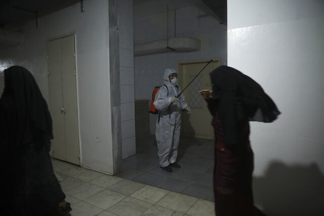 FILE - In this March 19, 2020 file photo, a member of a humanitarian aid agency disinfects inside Ibn Sina Hospital as prevention against the coronavirus in Idlib, Syria. Hospitals in Syria's overcrowded opposition-held enclave are suspending non-emergency procedures and outpatient services following the detection of the first case of coronavirus. A leading doctor in the area said on Friday, July 10, 2020 that the measures will last at lest a week. (AP Photo/Ghaith Alsayed, File)