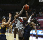 Virginia Tech's Justyn Mutts, center, drives past Coppin State defenders Isaiah Gross, left, and Anthony Tarke (3) in the first half of an NCAA basketball game in Blacksburg, Va., Saturday, Dec. 19 2020. (Matt Gentry/The Roanoke Times via AP, Pool)