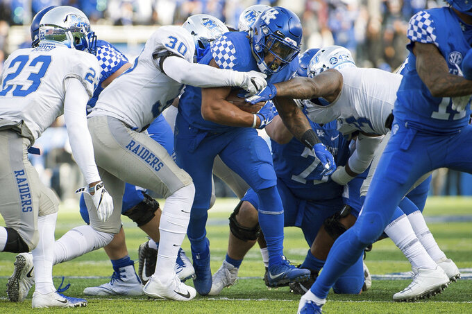 Kentucky running back Benny Snell Jr. (26) is tackled by Middle Tennessee linebacker Darius Harris (30) and defensive end Jahmal Jones (43) after a short gain during the second half of an NCAA college football game in Lexington, Ky., Saturday, Nov. 17, 2018. (AP Photo/Bryan Woolston)