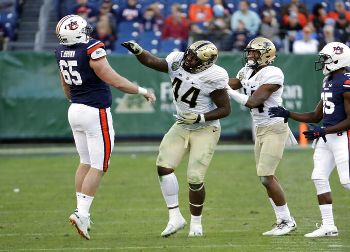 Purdue defensive tackle Anthony Watts (44) jabs Auburn's Tucker Brown (65) in the second half of the Music City Bowl NCAA college football game Friday, Dec. 28, 2018, in Nashville, Tenn. Watts was given an unsportsmanlike penalty. (AP Photo/Mark Humphrey)