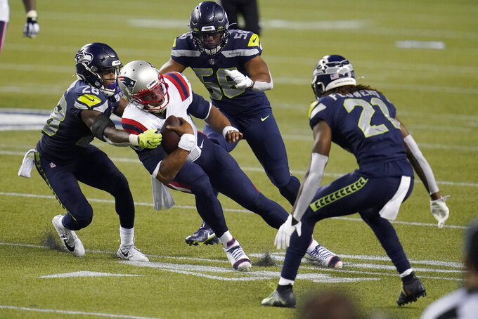 New England Patriots quarterback Cam Newton is tackled by Seattle Seahawks safety Ugo Amadi, left, as linebacker Jordyn Brooks, second from right, and cornerback Tre Flowers, right, look on during the second half of an NFL football game, Sunday, Sept. 20, 2020, in Seattle. (AP Photo/Elaine Thompson)