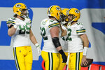 Green Bay Packers quarterback Aaron Rodgers, right, is congratulated by teammates after his 6-yard run for a touchdown during the second half of an NFL football game against the Detroit Lions, Sunday, Dec. 13, 2020, in Detroit. (AP Photo/Paul Sancya)