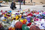 A woman is emotional at the scene of a small memorial left in remembrance to Kobe Bryant at the entrance of the Bryant Gymnasium at Lower Merion High School, Monday, Jan. 27, 2020, in Wynnewood, Pa.  The 41-year-old Bryant and his 13-year-old daughter, Gianna, were among nine people who died in the crash in Calabasas in foggy weather conditions Sunday morning.(AP Photo/Chris Szagola)