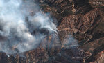 This natural color photo provided by Maxar Technologies shows fire spots from the Bobcat Fire amid an area of the Angeles Crest Highway winding through the San Gabriel Mountains, in Los Angeles County, California, Monday, Sept. 21, 2020. (Satellite image ©2020 Maxar Technologies via AP)