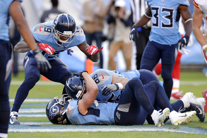 Tennessee Titans tight end Anthony Firkser (86) and wide receiver Tajae Sharpe (19) celebrate with wide receiver Adam Humphries, on the ground, after Humphries scored the winning touchdown against the Kansas City Chiefs in the fourth quarter of an NFL football game Sunday, Nov. 10, 2019, in Nashville, Tenn. The Titans won 35-32. (AP Photo/Mark Zaleski)