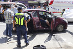 In this Oct. 18, 2019, handout photo provided by the Olongapo Public Information Office, police check on an Australian named Anthony George inside a car in Olongapo, northern Philippines. Philippine police city director of Olongapo city said they arrested Australian Michael McLaren shortly after the incident for the alleged killing of George and Filipino Mila Bailey inside the car. Another Australian victim, Wayne Bailey, is still recovering at the hospital from gunshot wounds. (Olongapo Public Information Office via AP)