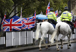 Police horses pass a confusion of flags and banners both pro and against Brexit, outside Parliament in London, Monday, Oct. 21, 2019. The European Commission says the fact that British Prime Minister Boris Johnson did not sign a letter requesting a three-month extension of the Brexit deadline has no impact on whether it is valid and that the European Union is considering the request. (AP Photo/Kirsty Wigglesworth)
