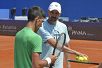 In this photo taken June 18, 2020, former Wimbledon champion Goran Ivanisevic, left, who now coaches top-ranked Novak Djokovic, right, attends a training session during an exhibition tournament in Zadar, Croatia. The Croatian great, who won his only Grand Slam title at the All England Club in 2001, wrote on Instagram that he tested positive for coronavirus after two negative tests in the last 10 days. (AP Photo/Zvonko Kucelin)