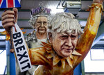 Figures depicting British Prime Minister Boris Johnson, right, and the Queen Elizabeth II are shown during a press preview for the Mainz carnival, in Mainz, Germany, Tuesday, Feb. 18, 2020. (AP Photo/Michael Probst)