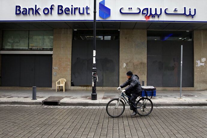 In this Wednesday, March 18, 2020 photo, a food deliveryman rides his bicycle past a Bank of Beirut branch that has been shut down as part of the preventive measures against the coronavirus, in Beirut, Lebanon. The COVID-19 pandemic has managed to do what various wars could not: Close bars, restaurants and entertainment spots across the tiny Mediterranean country. It's another economic gut punch, delivered at a time when Lebanon is mired in the worst financial crisis in its history -- one that could hasten the country's long-feared economic collapse. (AP Photo/Bilal Hussein)