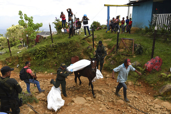 A police officer helps transport the body of one of at least five people killed during a skirmish between illegal armed groups in Jamundi, southwest Colombia, Friday, Jan. 17, 2020. Authorities say rebels with the former Revolutionary Armed Forces of Colombia operate in the area and may have been involved. (AP Photo/Christian EscobarMora)