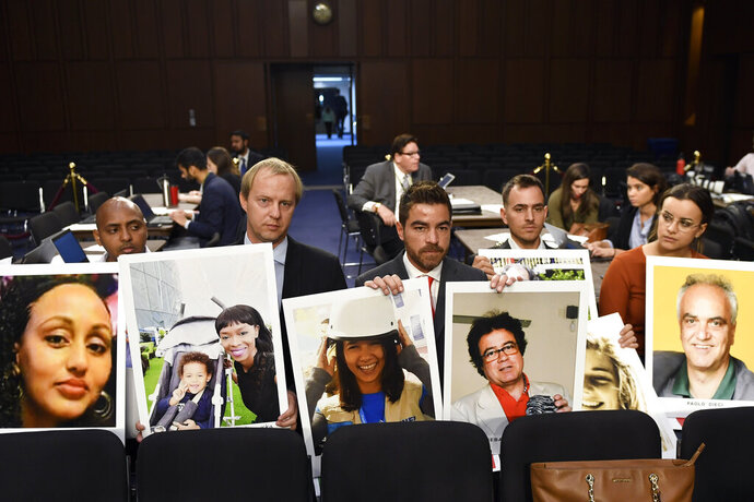 FILE - In this Oct. 29, 2019, file photo people holding photos of those lost in Ethiopian Airlines Flight 302 and Lion Air Flight 610 wait for the start of a Senate Committee on Commerce, Science, and Transportation hearing on Capitol Hill in Washington. (AP Photo/Susan Walsh, File)