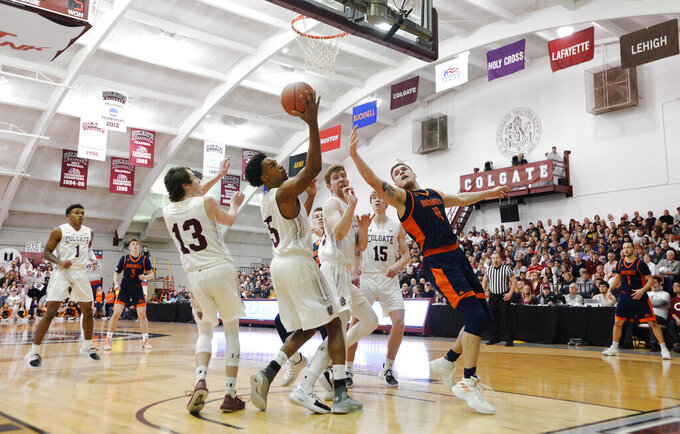 Colgate forward Malcolm Regisford (5) reaches for a rebound next to Bucknell center Nate Sestina (4) during the first half of an NCAA college basketball game for the championship of the Patriot League men's tournament in Hamilton, N.Y., Wednesday, March 13, 2019. (AP Photo/Adrian Kraus)