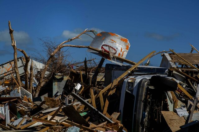 FILE - In this Sept. 27, 2019 file photo a basketball board is seen next to a car among the debris left by Hurricane Dorian, in a neighborhood destroyed by the storm in Abaco, Bahamas. Any concern about whether it was appropriate to be playing sports in the Bahamas while parts of the multi-island nation continue to recover from the effects of the storm was quickly dispelled by officials. Officials are hoping tourism and upcoming sporting events aid recovery efforts by boosting the economy to pay for reconstruction and raising awareness for people to donate or volunteer for ongoing work. Participants in those events _ including the eight-team Atlantis tournament opening Wednesday, Nov. 27, 2019 are also helping in the recovery. (AP Photo/Ramon Espinosa)